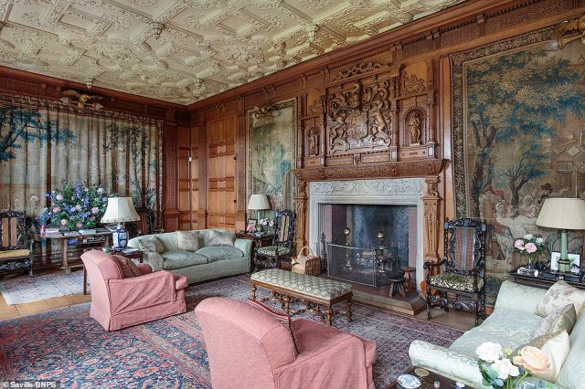 The drawing room, also built in the early 1900s, has intricate craftsmanship throughout with detailed woodwork and the family crests above the fireplace