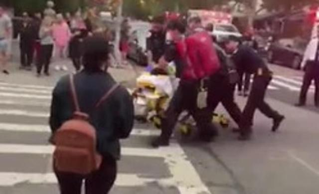 Medics are seen wheeling one of the victims away from the scene on a gurney. One neighbor told DailyMail.com the woman was 'green'