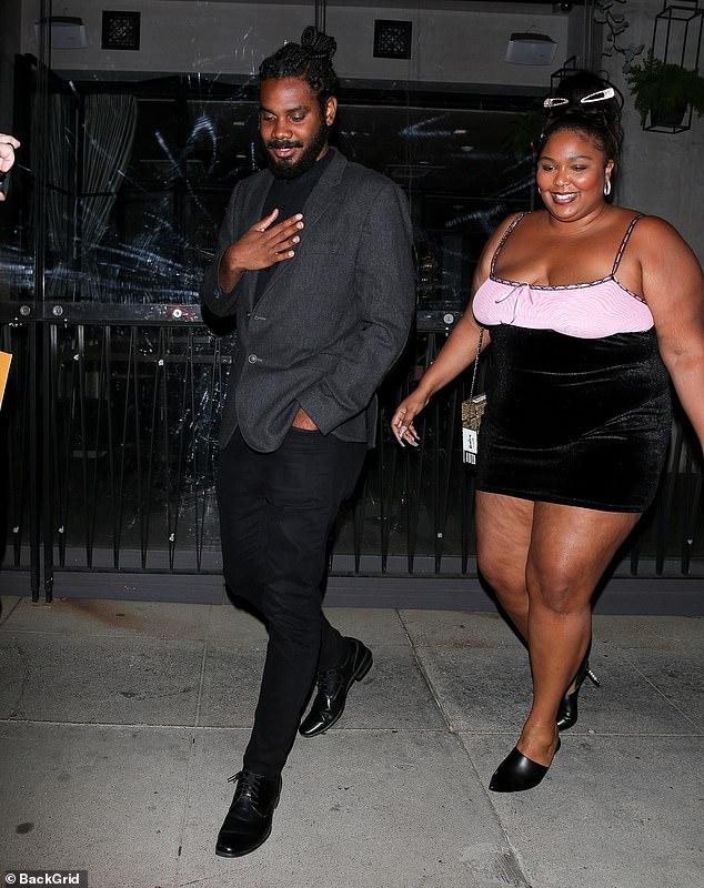 Skimpy: Lizzo (born Melissa Jefferson) looked cute in her dress, which featured a striking black velvet skirt that only reached down to her thighs and a pink top
