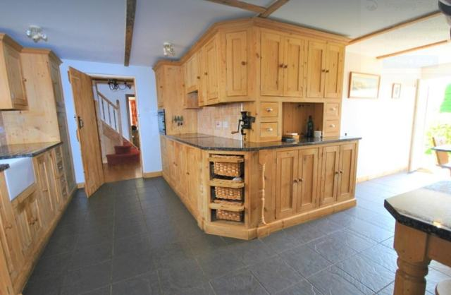 The kitchen, pictured, is hand-built and features solid granite worksurfaces and has a breakfast bar area