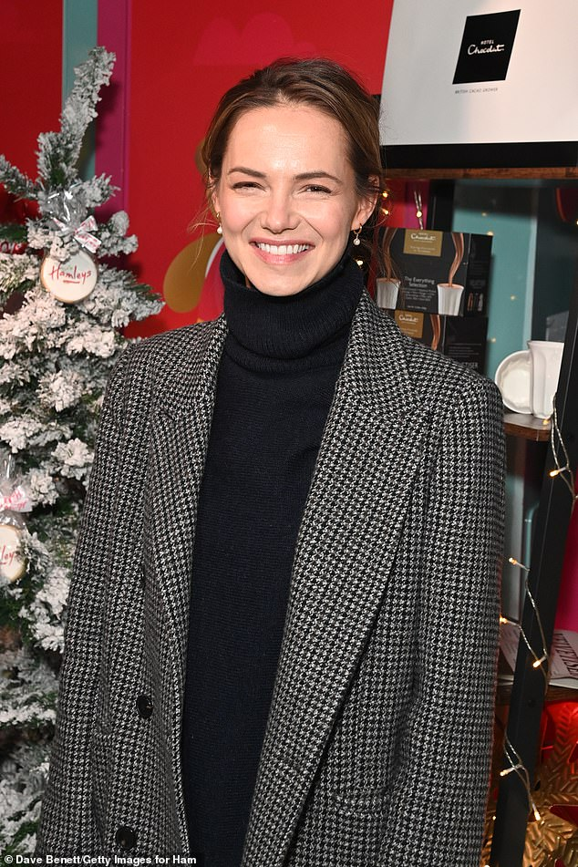 Festive spirit: Kara went more low-key, in a black turtleneck over flared jeans and a black and white checkered trench coat