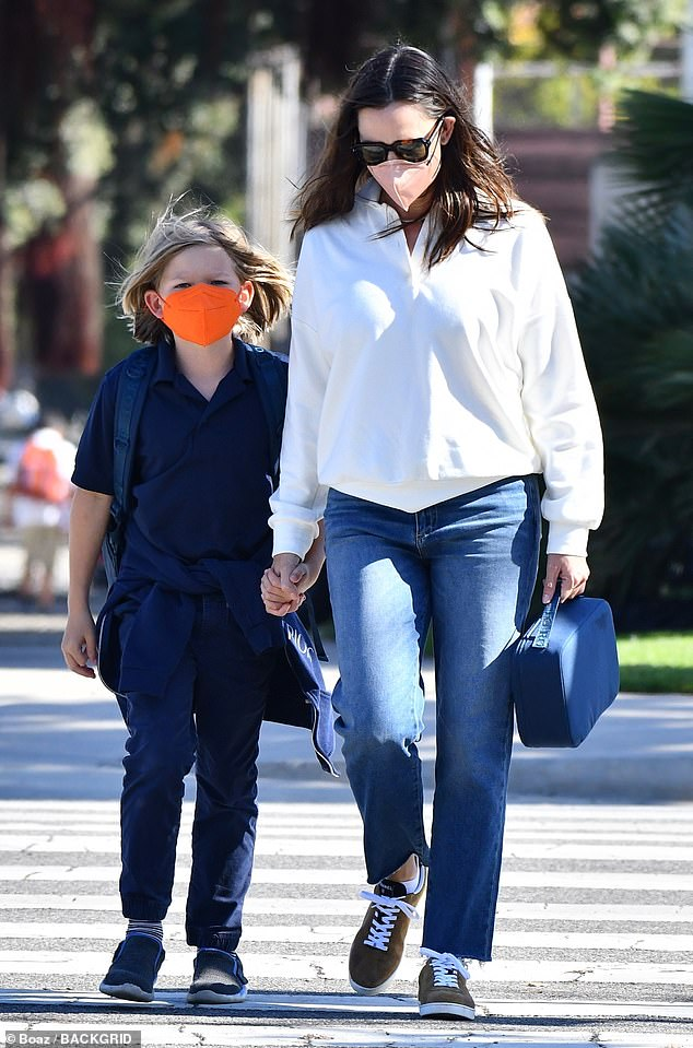 On the go: The mother-of-three kept it casual in blue jeans and a white long-sleeve shirt for her busy day with her son