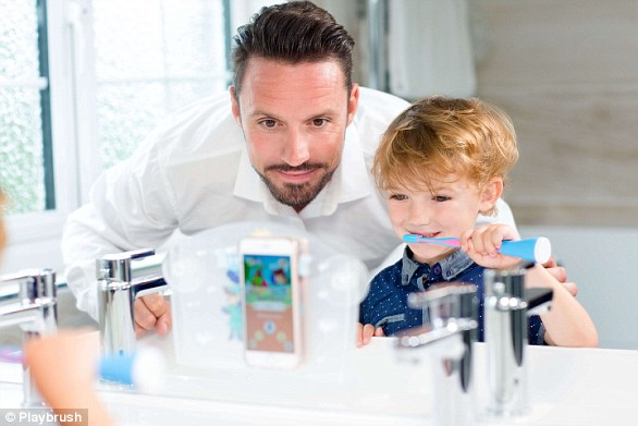 The toothbrushconnects via bluetooth to a games app that can be played on either a phone or an iPad, which can be attached to a bathroom mirror for ease, pictured.The game is controlled by the movement of the child's toothbrush and built-in motion sensors measure toothbrushing positions, speed and duration