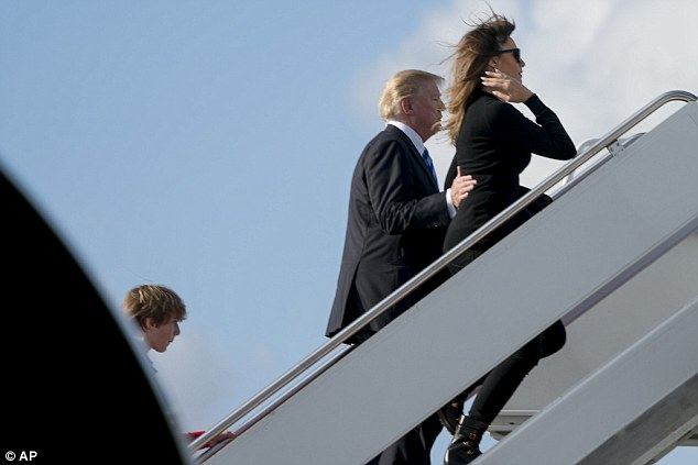 President Trump (center) guides first lady Melania Trump (right) up the stairs to the plane as Barron Trump (left) follows his parents on board