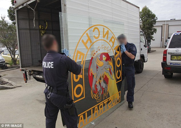 Police load a Comanchero sign onto a truck as they undertake raids against the gang in 2013