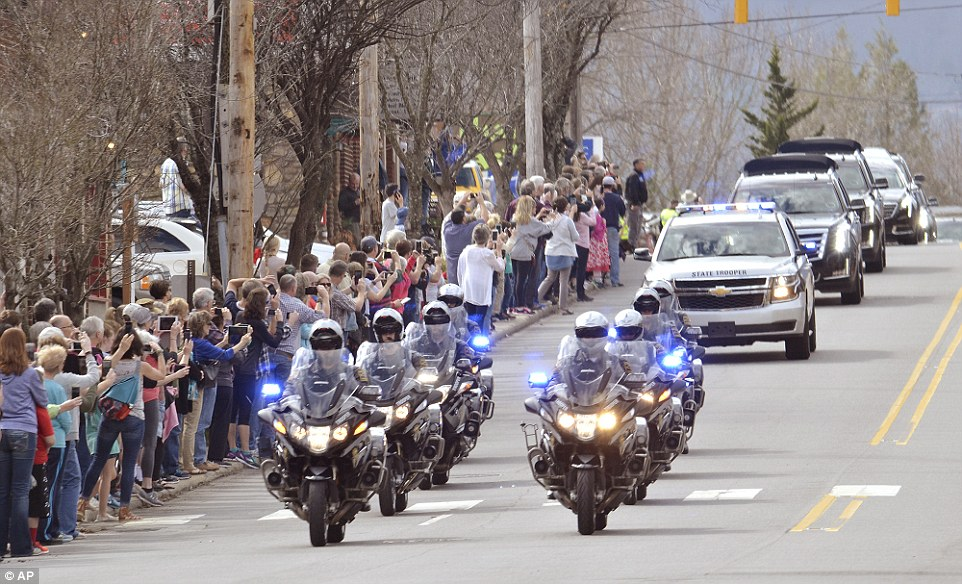 Mourners line Hwy 70 through Black Mountain, North Carolina as the motorcade carrying Rev. Billy Graham drives by