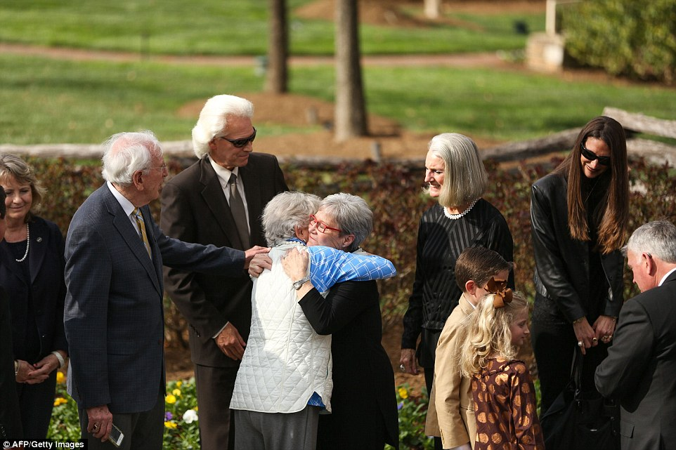 Family members are seen embracing one another.His grieving daughter Anne Graham Lotz is pictured second from the right