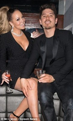 Steamy: Bryan was snapped caressing Mariah's leg as they posed for a photo together