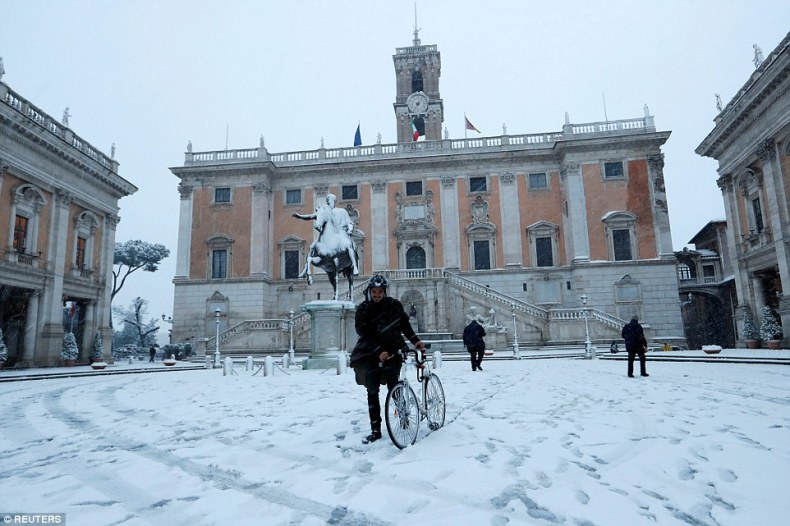 A man walks his bicycle through the snow in downtown Rome, Italy, after the city was hit by the first snowfall in six years