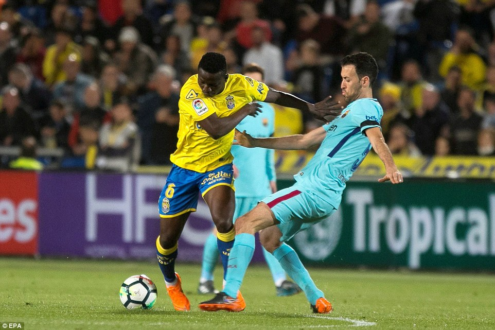Barcelona midfielder Sergio Busquets puts his foot in to try and win the ball off of opposition player Oghenekaro Etebo