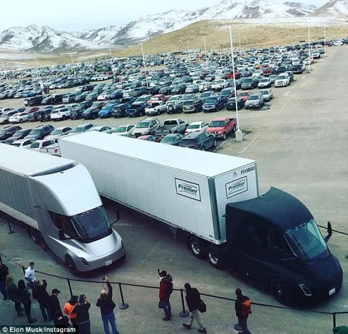 Elon Musk shared a photo today showing two of the electric big rigs side-by-side in the Gigafactory parking lot in Nevada, gearing up for their first production cargo trip. The black and silver trucks are towing battery packs to the firm¿s California factory