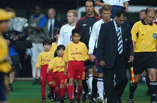 Former England captain David Beckham walks out with a mascot during the 2002 World Cup