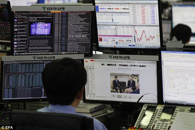 Market effect: A South Korean dealer works in front of monitors at the KEB Hana Bank in Seoul, South Korea