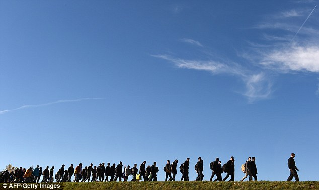 Los inmigrantes caminan hasta el primer punto de registro de la policía federal alemana después de cruzar la frontera entre Austria y Alemania en la pequeña aldea bávara de Simbach en septiembre de 2015.