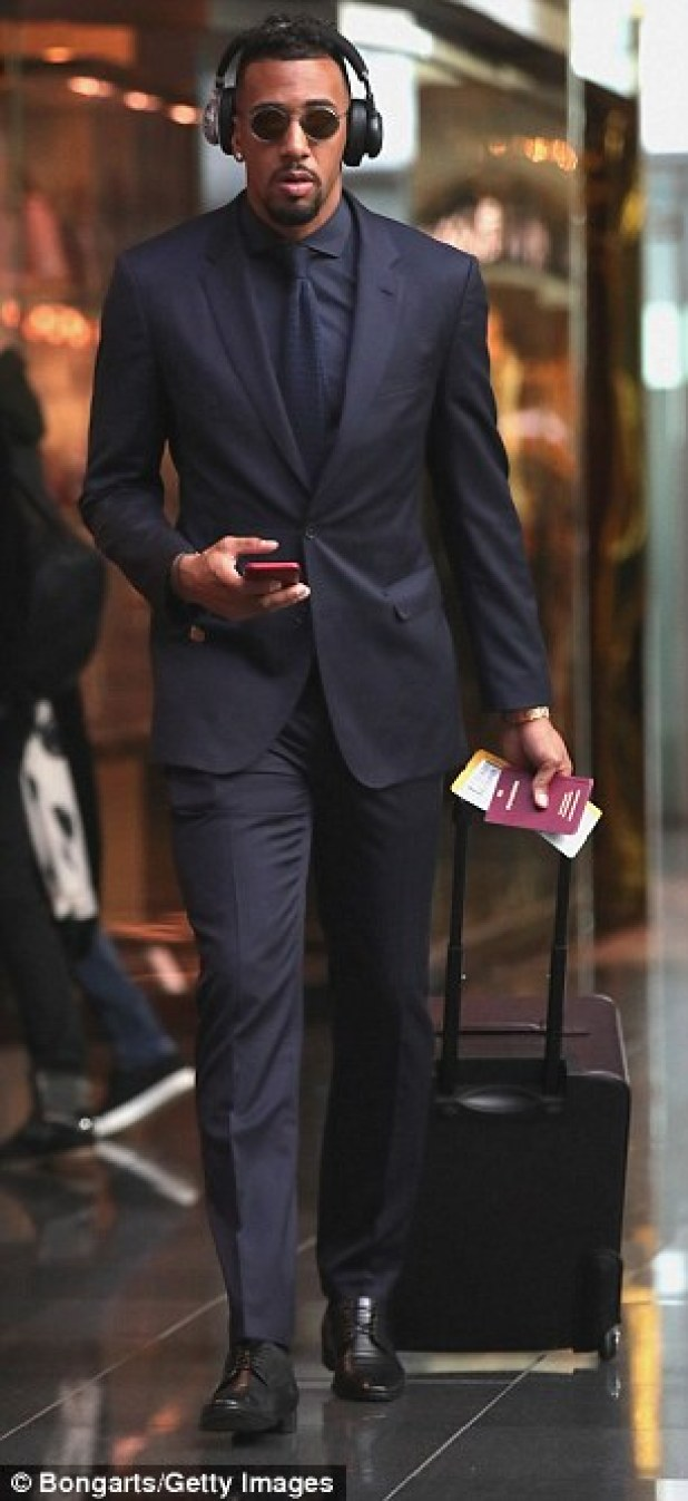 Defender Jerome Boateng looks sharp as he heads to the departures lounge at Munich international airport