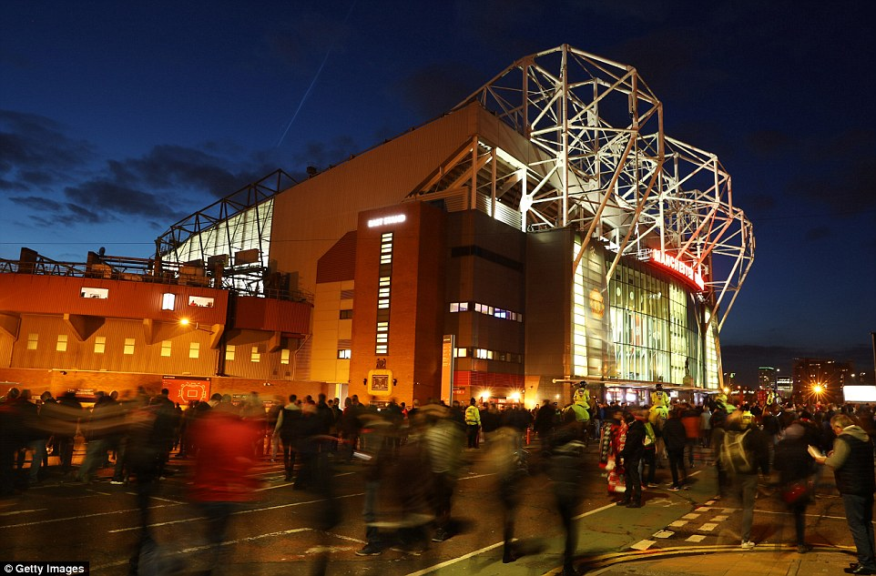 Supporters mill outside of a well lit Old Trafford ahead of kick-off in the last-16 second leg on Tuesday evening