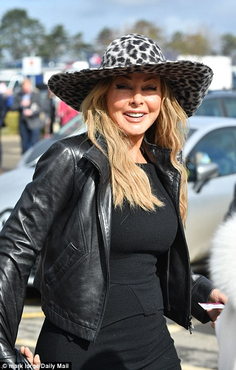 Carol Vorderman looked glamorous in a black dress and leather jacket teamed with a statement leopard print hat