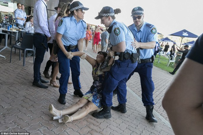 One reveller had to be held to her feet by three police officers at Rosehill Racecourse on Saturday afternoon (pictured)