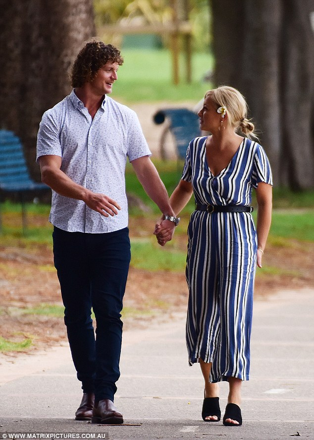 Romantic! The former rugby player, 30, looked smitten as he held hands with his glamorous companion during a romantic stroll through a park in Manly, Sydney