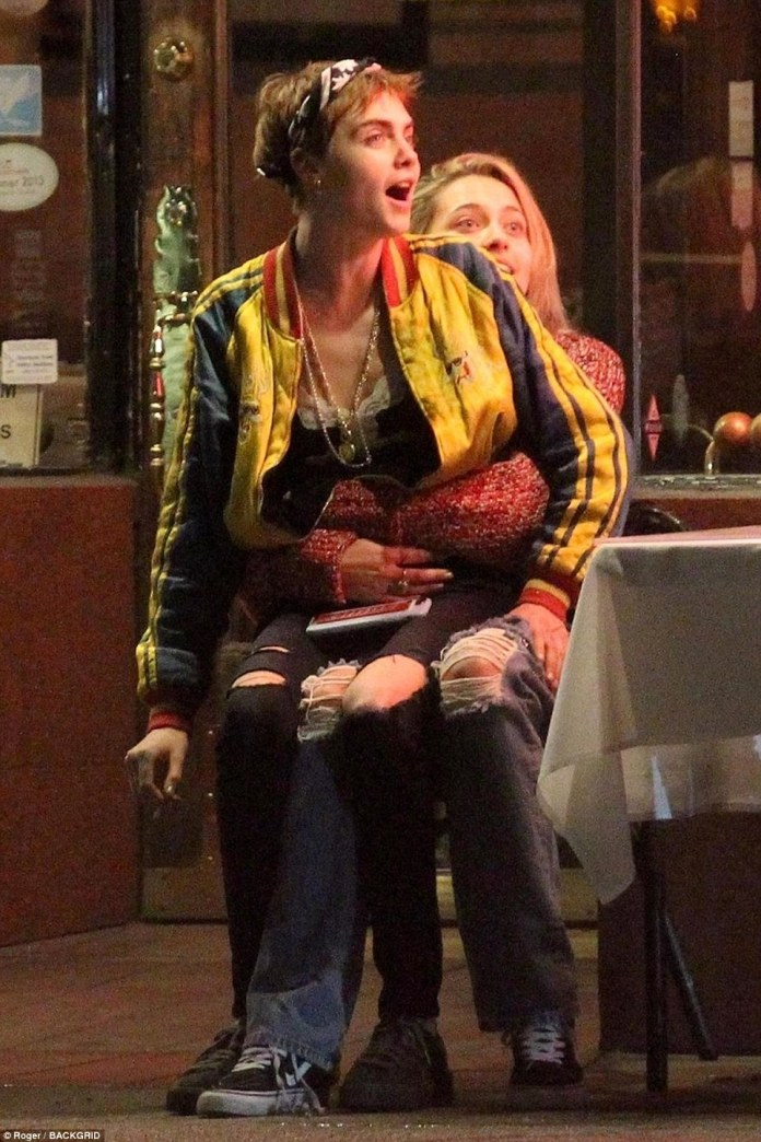 Sharing a seat: Cara then perched on Paris' lap as they shared a cigarette