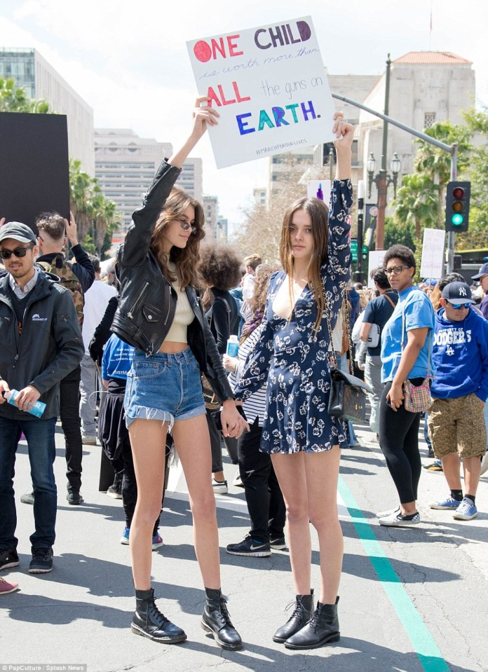 Model Kaia Gerber is spotted out at the March for our Lives rally with a friend in Los Angeles holding sign that reads 'One child is worth more than all the guns on the earth'