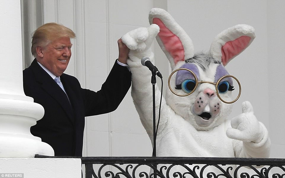 President Trump (left) holds up the hand of the Easter Bunny (right) as he briefly speaks at the White House's annual Easter Egg roll