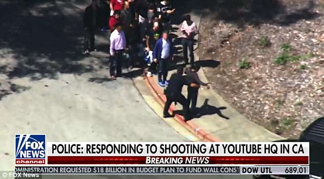 Employees are pictured being frisked outside YouTube HQ on Tuesday after shots were fired