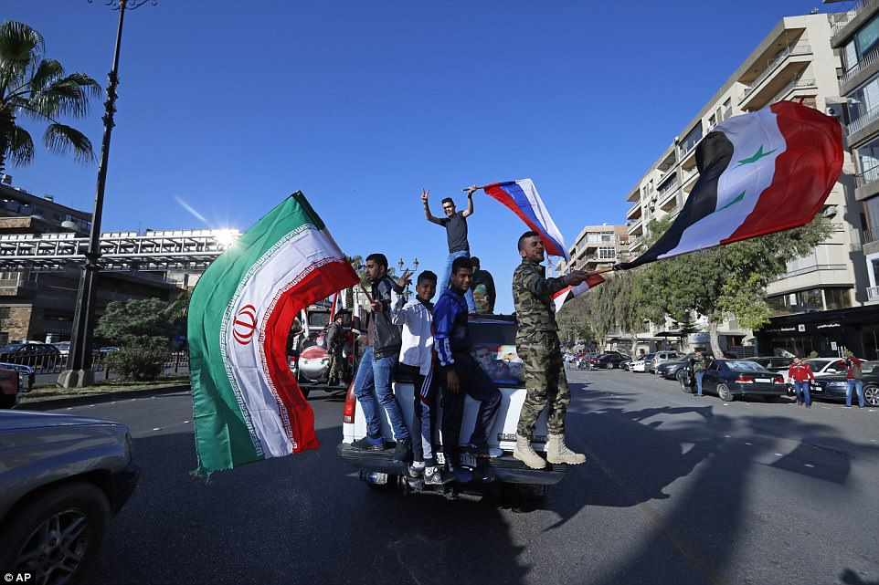 Syrian government supporters wave Syrian, Iranian and Russian flags as they chant slogans against U.S. President Trump during demonstrations