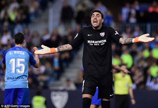 Malaga goalkeeperRoberto protests to the referee after a decision goes against his side