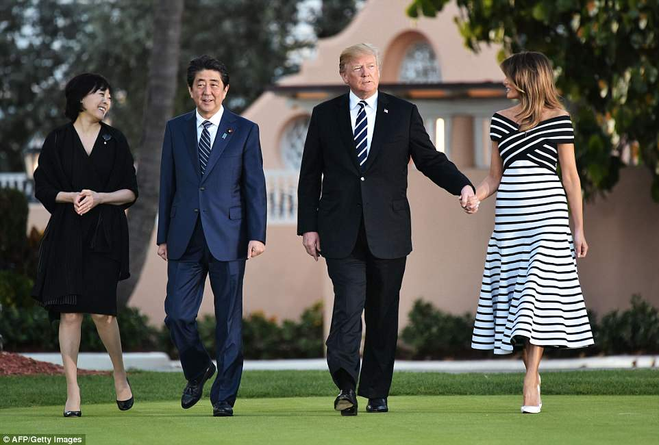 Trump and First Lady Melania Trump are seen holding hands as the two couples stroll across the lawn at Mar-a-Lago on Tuesday