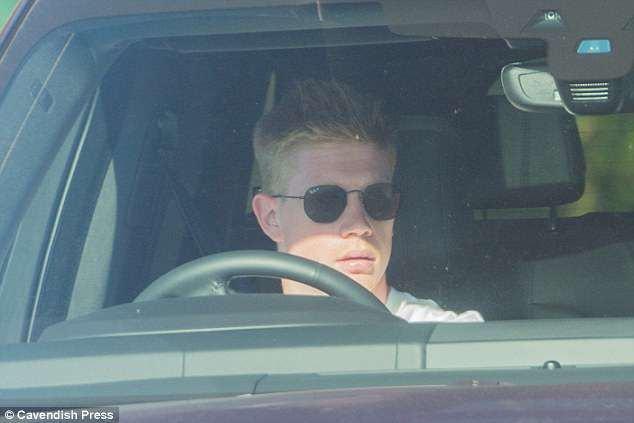 Kevin De Bruyne employs a pair of Ray Ban sun glasses as he blocks out the sun