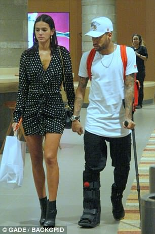Neymar, using a crutch, goes shopping in Rio de Janeiro with his girlfriend Bruna Marquezine