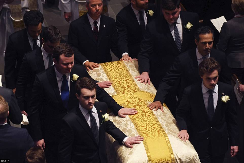 Barbara's grandsons place a tender hand on her casket as it is led out of the church on Saturday after her funeral