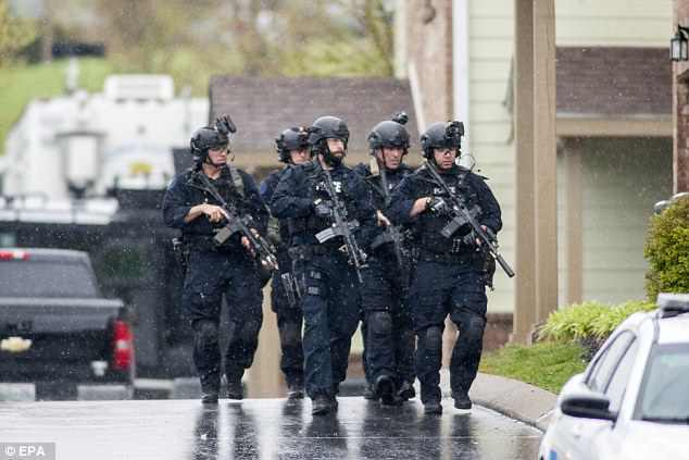 Swat members with assault weapons could be seen patrolling the neighborhood on Sunday
