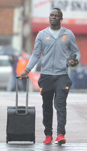 Sadio Mane listens to music while wheeling his suitcase across the Anfield car park