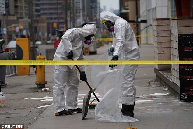A work crew in protective clothing cleans a sidewalk a day after a van struck multiple people along a major intersection in north Toronto, Ontario