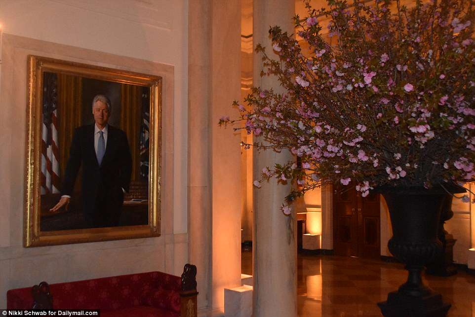 President Bill Clinton's portrait hangs next to one of Melania Trump's giant vases of cherry blossoms. Despite their political differences, the first lady used the Clinton china as part of her first state dinner's place settings