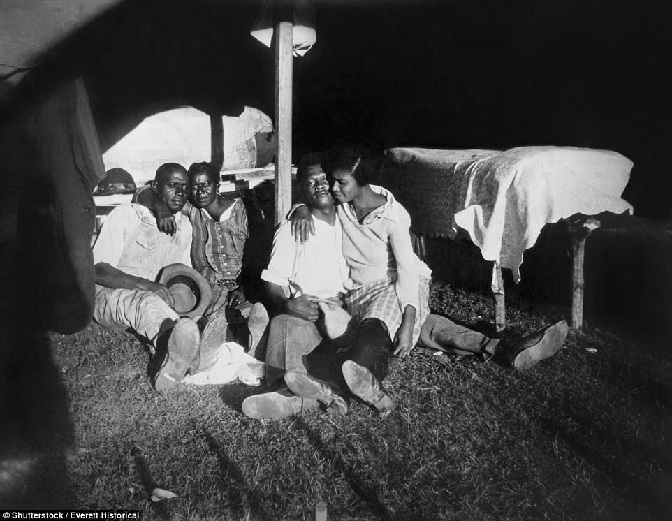 Two African American couples take refuge in a tent during the 1927 Mississippi River flood at a refugee camp in Vicksburg National Military Park