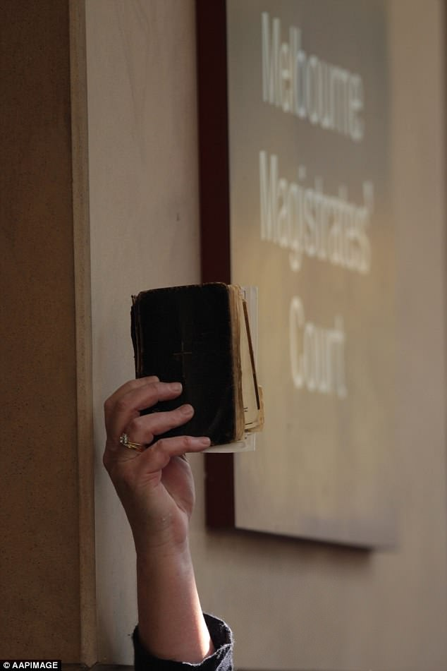 A bible is held up by a member of the crowd gathered in front of the court