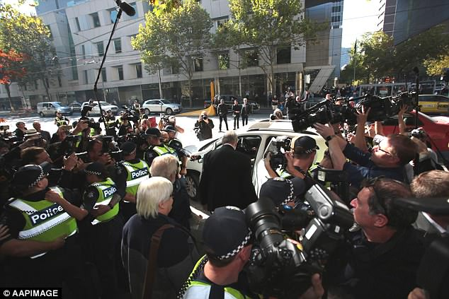 Australia's most senior Catholic cleric has strenuously denied all charges and was in court on Tuesday to plead not guilty (pictured is Pell surrounded by police and media after court on Tuesday)