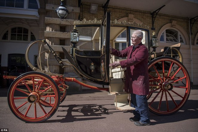Martin Oates, senior carriage restorer, polishes the Scottish State Coach, which will be used in the case of wet weather