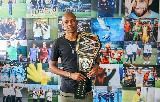 Fernandinho looks enthused as he holds the custom-made WWE championship title belt