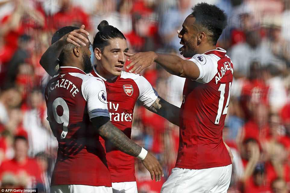 The forward (left) is congratulated by Hector Bellerin (centre) and Aubameyang after increasing his team's advantage