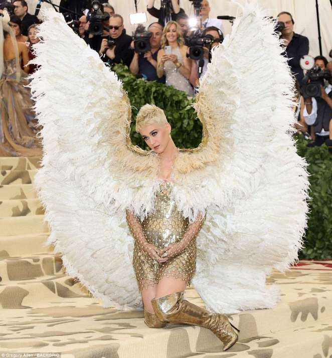 Katy Perry knelt as she posed for photographers while wearing her elaborate outfit, which came with feathered wings and golden boots