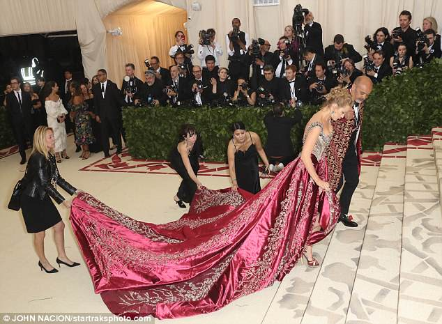 Actress Blake Lively was pictured with an army of assistants helping her with a sweeping train as she arrived at this year's Met Gala with Christian Louboutin