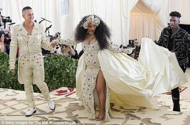Meanwhile, Cardi B also had the help of an assistant with her sumptuous gown by Moschino