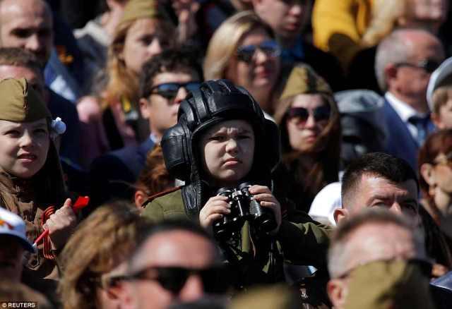 兵士や武器のパレードが終わると、群衆の中で戦車ヘルメットや双眼鏡の少年が腕時計を見る
