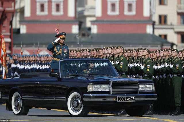 セルゲイ・ショイグ国防相は、組まれた軍隊を乗り越えたオープントップカーに乗って敬意を表する