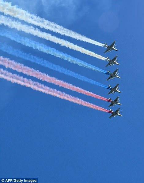 ロシアのSu-25襲撃機は、パレードの上空を飛行しながらロシアの旗の色で煙を放つ