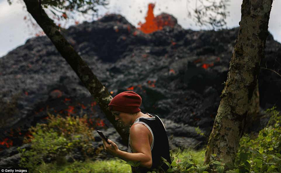 Following the eruption of Hawaii's Kilauea volcano, experts on the West Coast of America are now warning of potential volcanic eruptions involving the 13 volcanoes forming the Pacific's 'Ring of Fire.' Pictured above, a resident talks on his phone Saturday as a lava fissure erupts in the aftermath of eruptions from the Kilauea volcano